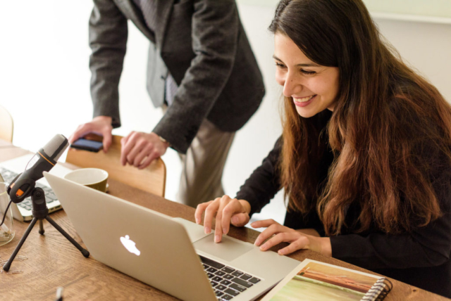 Small business owner working at laptop and chatting with business partner