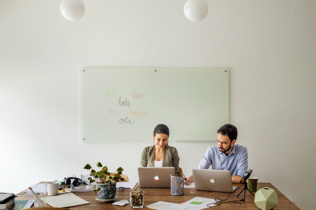 Two small business founders working on their laptops at a large wooden desk with a whiteboard behind them
