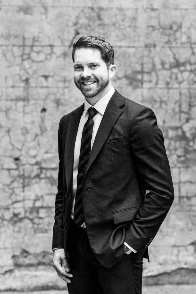 Black and white business portrait in front of a concrete wall