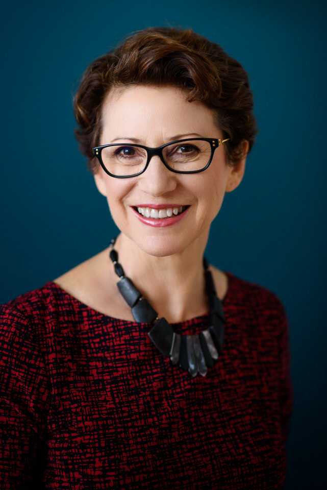 Business portrait of woman in glasses against blue background