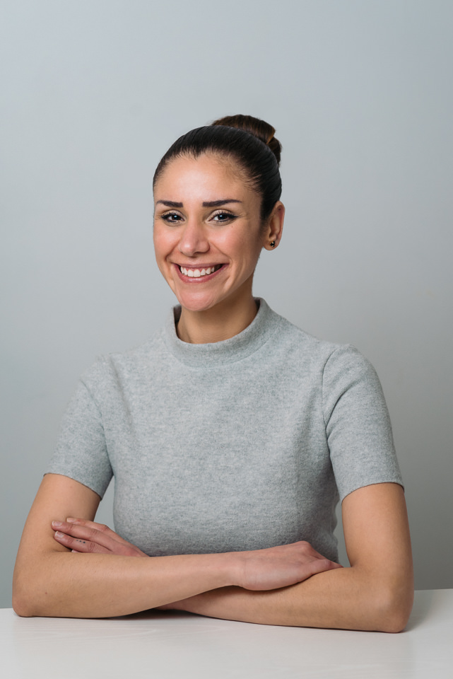 Business headshot of woman in grey sweater in white room